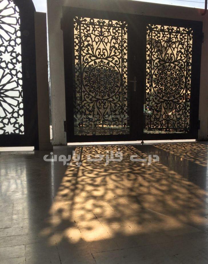 جلوه ای از زیبایی و انعکاس نور خورشید از شیشه های سکوریت نشکن بر روی درب فلزی برش لیزری