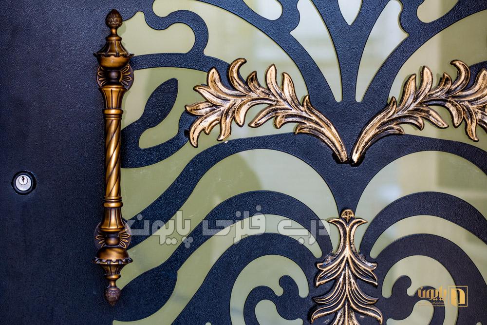 قطعات فلزی فرفورژه گل بر روی لنگه های درب